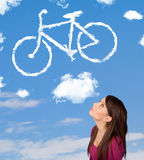 Girl looking at bicycle clouds on blue sky Stock Photos