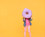 Girl looking through a big donut. Girl looking through a big violet donut over yellow background. Little kid holding a number zero with copy space. Null numeral royalty free stock photo