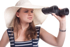 A girl looking through binoculars. A girl in a big straw hat looking through binoculars on a white background Stock Images