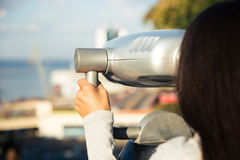 Girl looking in binoculars at the city Royalty Free Stock Photos