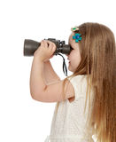 Girl looking through binoculars. Cute little long-haired girl turned sideways to the camera looking through binoculars . close-up - Isolated on white background Royalty Free Stock Photos