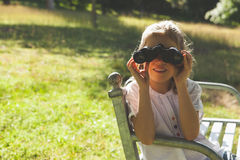 Girl looking through binoculars at park Royalty Free Stock Image