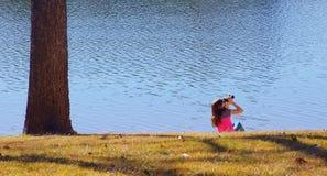 Girl looking through binoculars on water side royalty free stock photography