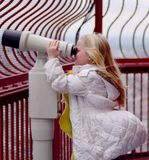Girl looking through binoculars. A wind-swept girl looking with binoculars through curved barriers, photographed at the top platform of Blackpool Tower, a well Stock Photography