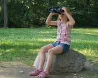 Girl looking through binoculars. Young girl with black binoculars Stock Photography