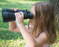 Girl looking through binoculars Royalty Free Stock Photography