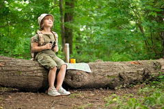 Girl looking birds through binoculars, camping in the woods Stock Photo