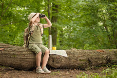 Girl looking at birds through binoculars, camping in the woods. Excited little girl on a camping trip in green forest Royalty Free Stock Photo