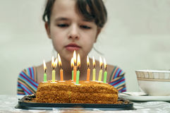 Girl looking at birthday cake with burning candles. Sad teen girl looking at birthday cake with burning candles Stock Photo