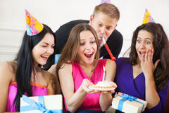 Girl looking at birthday cake surrounded by friends at party Stock Photos