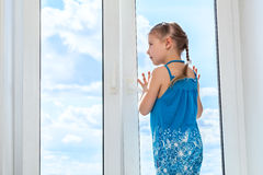 Girl looking at blue sky through window Royalty Free Stock Photography