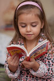 Girl looking at book. Portrait of little girl with a book Royalty Free Stock Image