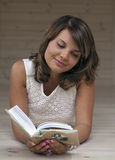 Girl  looking into a book. Girl lying on the floor and looking into a book Royalty Free Stock Photo