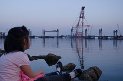 Girl are looking at the bridge which is building in the sea in the evening. Stock Photo