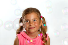 Girl looking at bubbles Stock Photos