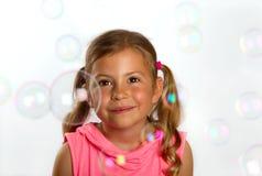 Girl looking at bubbles Stock Photos