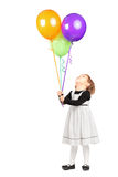 Girl looking at bunch of balloons Stock Photos