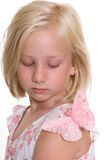 Girl Looking at Butterfly on her Shoulder. Young, 8 year old blonde girl  wearing a white and pink floral dress, is looking down at a pink butterfly that has Royalty Free Stock Photo