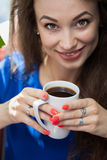 Girl looking in the camera with a cup of coffe in hands Stock Photography