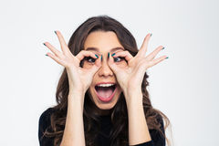 Girl looking at camera through fingers Stock Photos