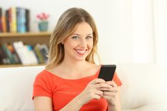 Girl looking at camera holding a smart phone at home. Blonde happy girl looking at camera holding a smart phone sitting on a sofa in the living room at home royalty free stock photos