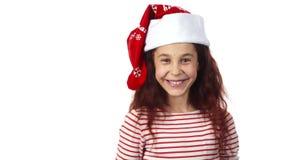A girl in a Santa Claus cap smiles at the camera royalty free stock image
