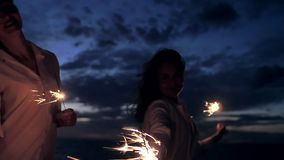 Girl looking at the camera and twist sparklers stock video