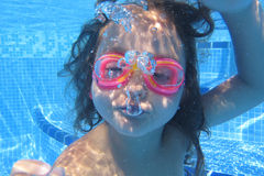 Girl looking at camera underwater Stock Photos