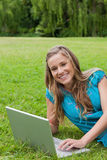 Girl looking at the camera while using her laptop Royalty Free Stock Photography