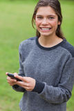 Girl looking at the camera while using her mobile Royalty Free Stock Photography
