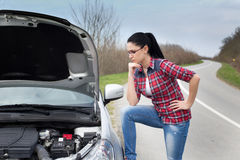 Girl looking car with open hood Royalty Free Stock Image