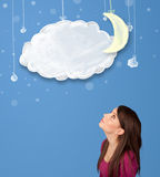 Girl looking at cartoon night clouds with moon hanging down Stock Images