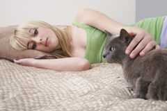 Girl Looking At Cat While Lying In Bed Stock Photo
