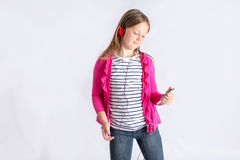 Girl looking at cell phone with headphones Royalty Free Stock Photography