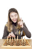 Girl Looking At The Chessboard With A Forefinger Up, She Is Very Happy With Her Strategy Plan How To Win The Game,Got Idea Gesture Royalty Free Stock Photos