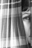 Girl looking through a chink in curtains. Close-up of a girl looking through a chink in checked curtains, with a part of her face and one eye only Stock Photo