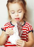 Girl looking at chocolate wrapped in tinfoil and opening it. Girl looking at sweet chocolate, wrapped in tinfoil, in the proccess of opening it, concentrated kid Stock Photo