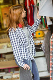Girl looking at clothes while holding her skateboard Stock Images