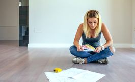 Girl looking color chart. Sitting on the floor stock photos