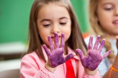 Girl Looking At Colored Hands In Art Class. Little girl looking at colored hands with female friend in art class stock photography