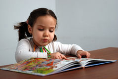 Girl looking in a colorful story book. Young girl looking in a colorful story book for children Royalty Free Stock Photo