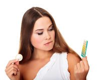 Girl looking at condom and contraceptive pills. Confused pretty caucasian girl looking at condom and contraceptive pills stock images