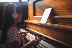 Girl looking at digital tablet while practicing piano in classroom Stock Photos