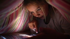 Girl Looking At Digital Tablet In Under Bed Cover At Night Royalty Free Stock Images