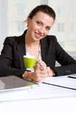 Girl in looking documents drinking coffee and smiling Stock Photo