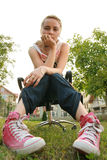 Girl looking down. Girl sitting on chair looking at camera Royalty Free Stock Photos