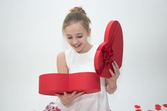 Girl looking down into a box containing a gift she received for Valentine`s day stock images