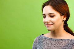 Girl looking down on green background Stock Photo