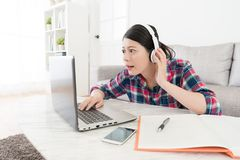 Girl looking at e-learning system teaching video. Lovely young girl looking at e-learning system teaching video and using headphone carefully listening how to Royalty Free Stock Images