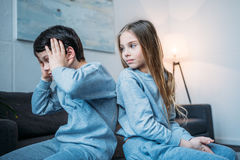 Girl looking at emotional brother with hands on head at home. Little girl looking at emotional brother with hands on head at home royalty free stock photos